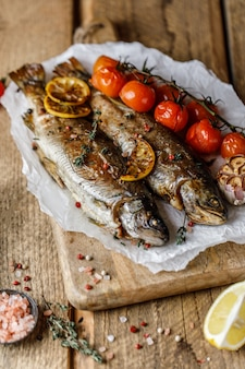 Truta do rio cozida com especiarias e ingredientes para cozinhar em fundo rústico