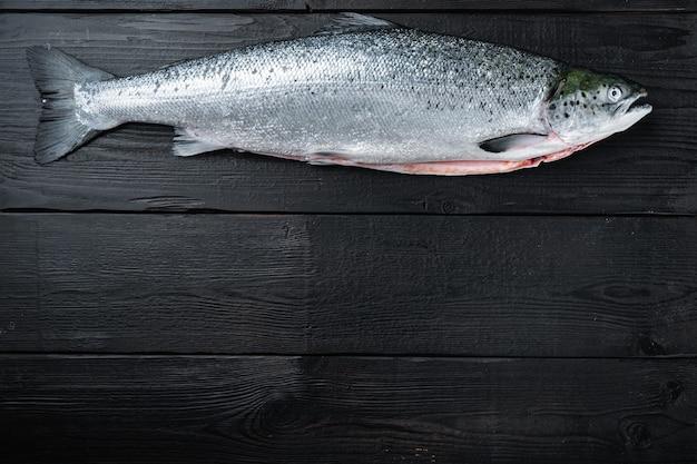 Truta fresca crua de peixe vermelho em madeira preta