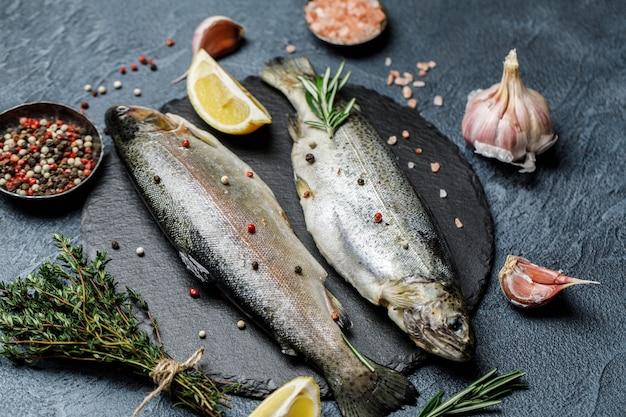 Truta fresca do rio com especiarias e ingredientes para cozinhar em fundo de pedra escura