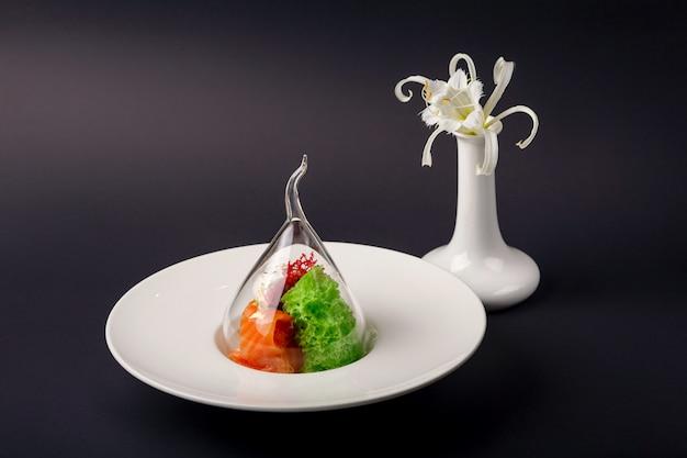 Truta gravlax de cozinha molecular com sorvete de alho em um fundo preto