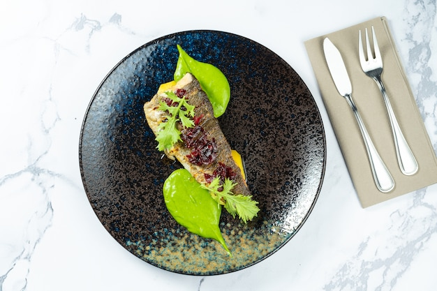 Truta grelhada com beterraba caramelizada e purê verde em um prato preto sobre uma mesa de mármore. frutos do mar. refeição com peixe.