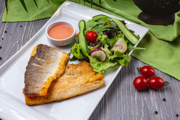 Truta grelhada peixe tomate pepino alface rabanete vista lateral