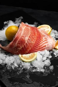 Truta ligeiramente salgada. filé de peixe fresco com ingredientes culinários, ervas e limão em um fundo preto, vista lateral.