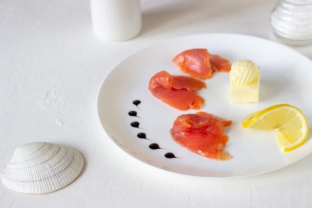Truta, manteiga e limão em um prato. fundo branco