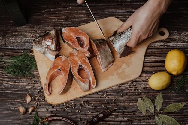 Truta na placa, que corta um homem cozinhar com uma faca, peixe fresco cru vermelho
