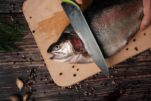 Truta no tabuleiro com uma faca cortando-a para cozinhar
