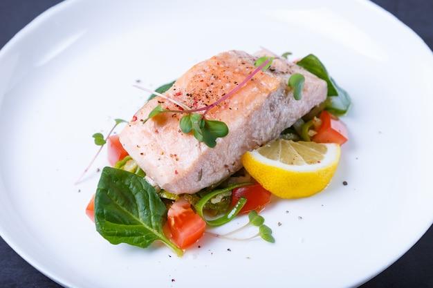 Truta (salmão) com legumes, limão e microgreens, cozida pelo método confitado. prato tradicional francês. passo a passo. fechar-se.