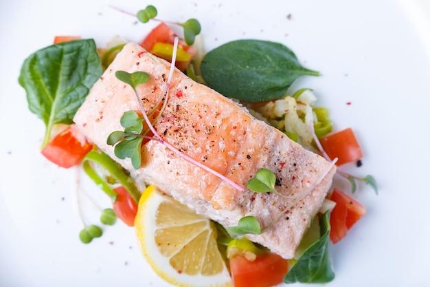Truta (salmão) com legumes, limão e microgreens, cozida pelo método confitado. prato tradicional francês. passo a passo. vista do topo.