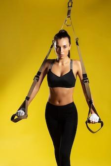 Trx exercita jovem mulher desportiva em roupas esportivas fazendo flexões com alças trx fitness contra