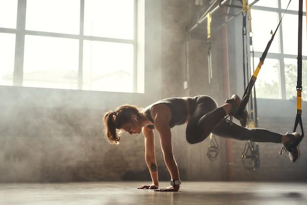 Trx treinando jovem atlética em roupas esportivas, treinando pernas com alças trx fitness em