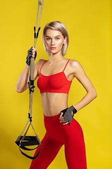 Trx treinando jovem e confiante mulher loira esportiva em uma roupa esportiva vermelha segurando alças de fitness e