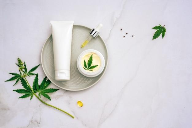 Tuba e frasco de óleo creme cbd, tintura de thc e folhas de cânhamo. postura plana, minimalismo.
