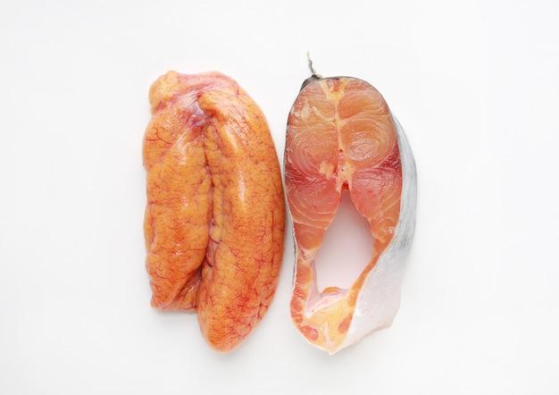Tubarão iridescente fresco cortado ou peixe-gato listrado com o ovo no fundo branco.
