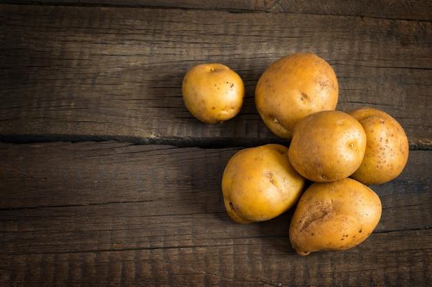 Tubérculos de batata fresca na mesa de madeira velha.