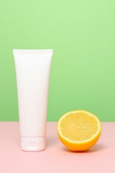 Tubo branco de creme facial e corporal com limão em fundo verde-rosa