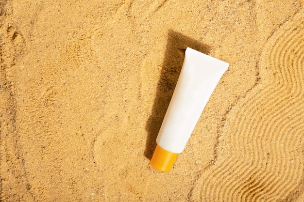 Tubo branco de protetor solar na areia da praia proteção solar vista superior copiar espaço