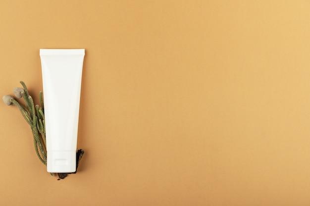 Tubo branco sem marca para creme, protetor solar ou loção hidratante e planta verde. produto cosmético ecológico. conceito de cosmetologia natural. isolado em um fundo bege, copie o espaço.