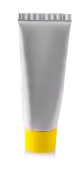 Tubo cinza com creme cosmético com tampa amarela isolado no fundo branco