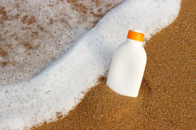 Tubo com protetor solar proteção spf na praia de areia. copie o espaço para o texto.