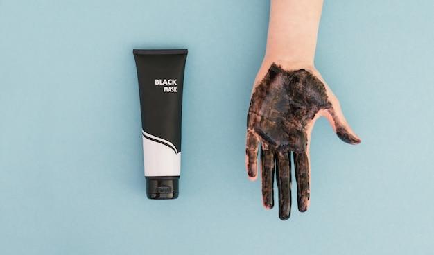 Tubo com uma máscara preta e uma mão feminina com uma máscara são isoladas em azul