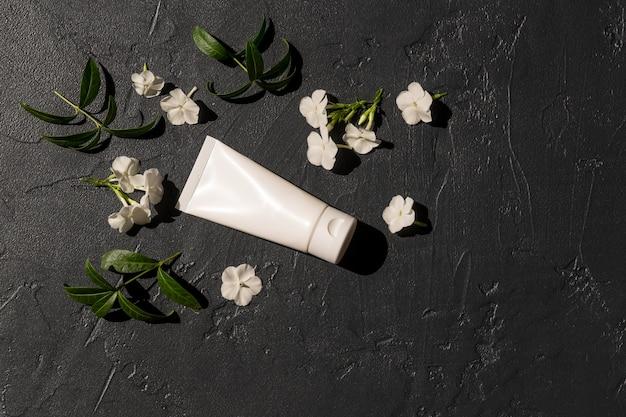 Tubo cosmético branco com creme para as mãos em um fundo escuro com folhas verdes e flores brancas. conceito de cosméticos com ingredientes à base de ervas