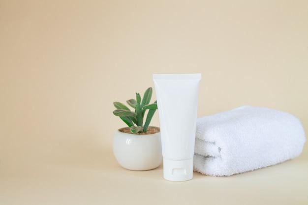 Tubo cosmético branco em branco ao lado da planta e da toalha