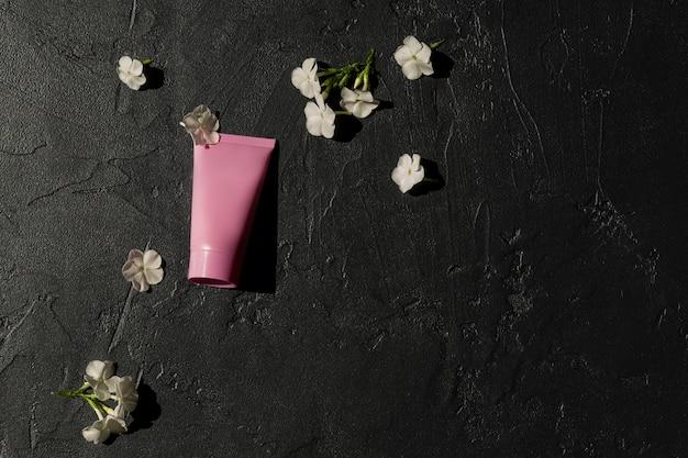 Tubo cosmético rosa com creme facial, loção corporal ou limpador em um fundo escuro com flores brancas desabrochando. conceito de cuidados com a pele sensível. copie o espaço, simule-se.