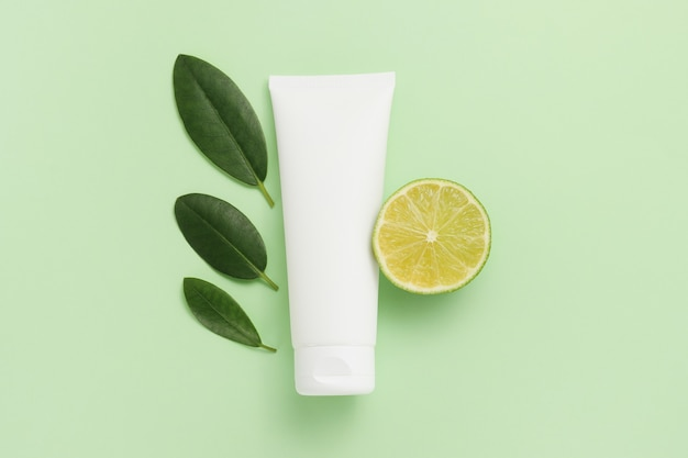 Tubo de creme branco com fatias de limão e folhas verdes sobre fundo verde