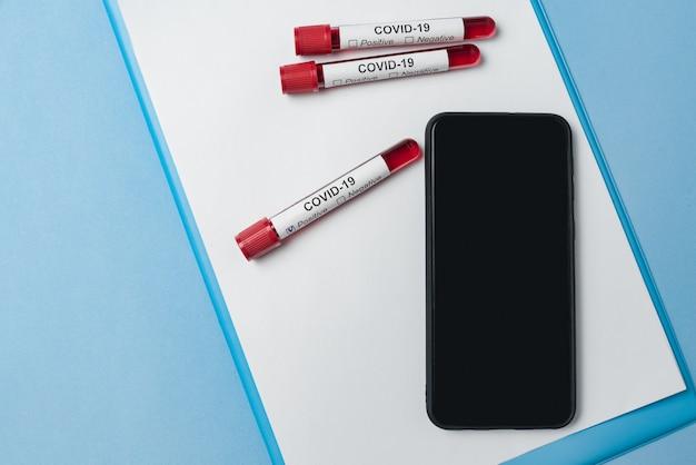 Tubo de ensaio com sangue para análise covid-19 e smartphone com tela preta vazia.