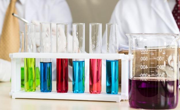 Tubo de ensaio de muitas cores no laboratório com os cientistas de volta à terra
