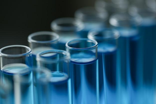Tubo de ensaio de vidro transborda nova solução líquida azul de potássio conduz uma reação de análise