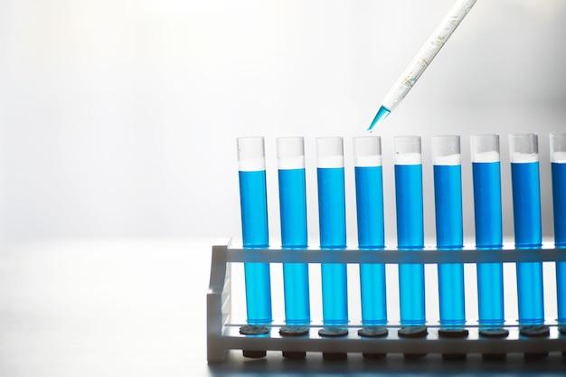 Tubo de ensaio de vidro transborda nova solução líquida de azul de potássio conduz uma reação de análise leva várias versões de reagentes usando fabricação de câncer químico farmacêutico.