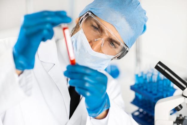 Tubo de ensaio nas mãos de um assistente de laboratório