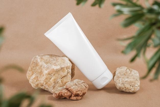 Tubo de frasco cosmético em branco branco em pedra emoldurado por folhas verdes de ramos, fundo bege. orgânico natural