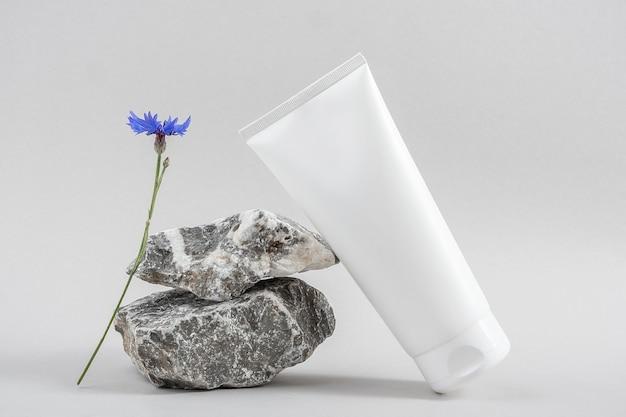 Tubo de frasco cosmético em branco branco na pedra e flor azul em fundo cinza. conceito de beleza cosmética de spa orgânico natural. vista frontal mock up.