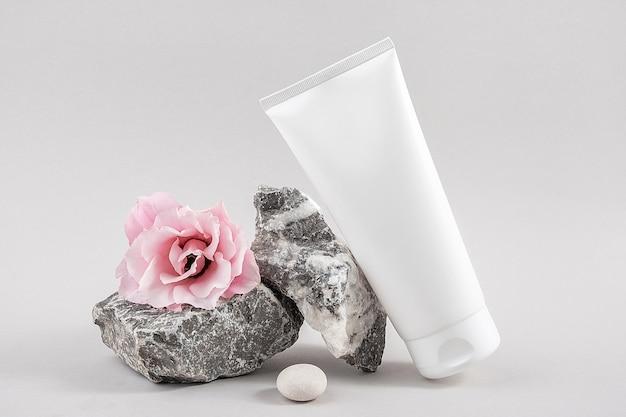 Tubo de garrafa cosmética em branco branco, pedra e flor rosa em fundo cinza. conceito de beleza cosmética de spa orgânico natural. vista frontal mock up.