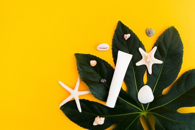 Tubo de maquete branco com estrela do mar e folhas verdes sobre fundo amarelo