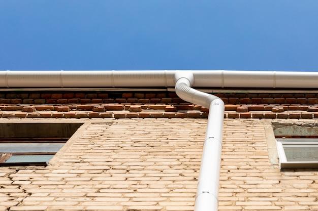 Tubo de metal branco do ralo na parede de um prédio de tijolos. sistema de drenagem de calha titular na cobertura. drene no telhado da casa. drenagem do telhado. drenagem de água do telhado.
