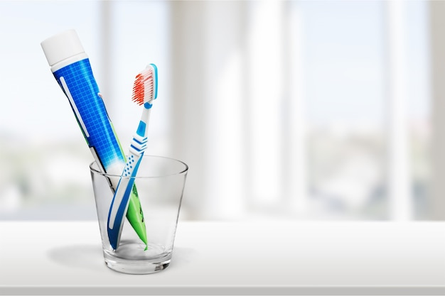 Tubo de pasta de dente e uma escova de dente em background