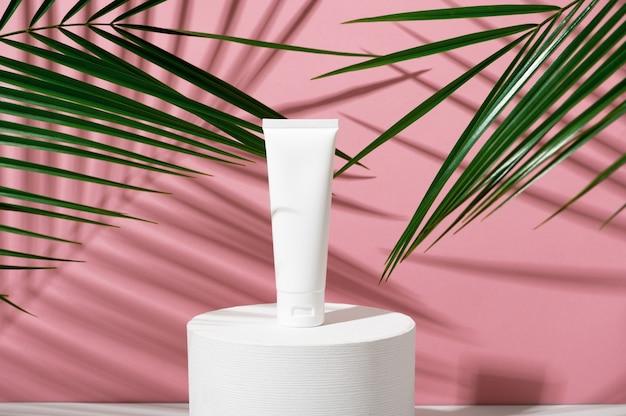 Tubo de plástico branco com creme em suporte geométrico redondo em um fundo rosa com palma