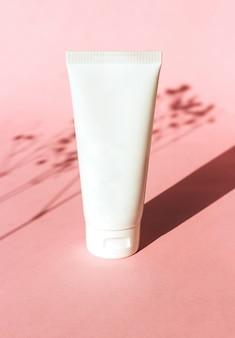 Tubo de plástico branco com creme para mãos e corpo em fundo rosa com sombra