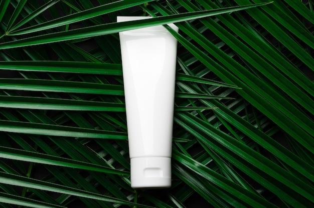 Tubo de plástico branco com creme para mãos, rosto e corpo em folhas de palmeira, cenário tropical. modelo de produto de cuidados da pele de beleza. fundo escuro, conceito de cuidados naturais, cosméticos ecológicos.