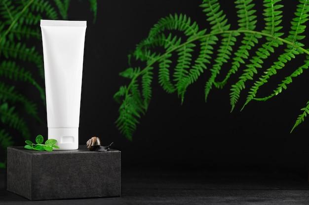 Tubo de plástico sem marca na vitrine. frasco para creme. folhas da floresta no pano de fundo. recipiente para cosméticos profissionais. produtos ecológicos e conceito de beleza. maquete, copie o espaço no lado direito.