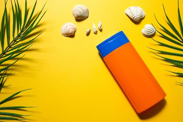 Tubo de protetor solar em um fundo amarelo de verão com folhas de palmeira e o sol. agente bronzeador, proteção para a pele, viagem ao mar, férias na praia, proteção uv, filtro fps. postura plana, copie o espaço