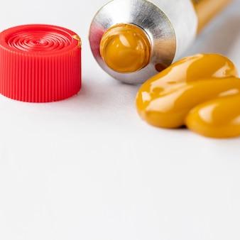 Tubo de tinta amarela e boné vermelho
