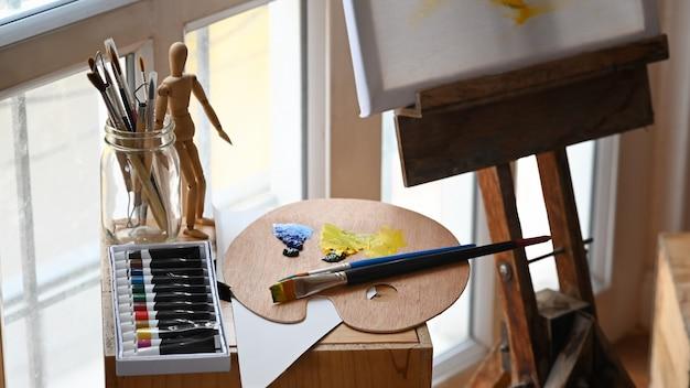 Tubo de tinta colorida, amostras de cores, pincel, fantoche, pincel em vaso e lona montando no estúdio do artista.