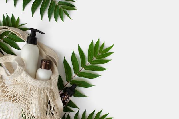Tubo em branco branco em sacola de compras eco em fundo branco com folhas de cosmético spa orgânico natural ...