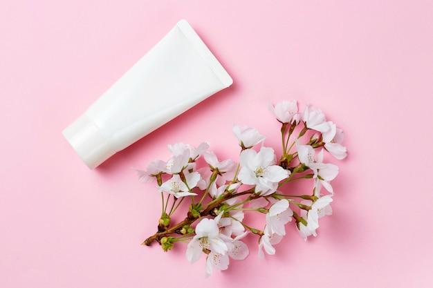 Tubo em branco com flores, conceito de cuidados de cosméticos