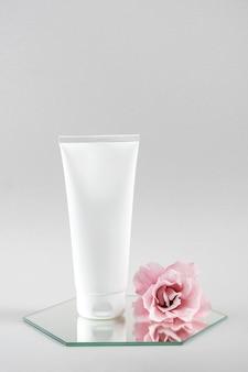 Tubo em branco cosmético branco e flor rosa no espelho, plano de fundo cinza. maquete do conceito de beleza cosmética natural organic spa, vista frontal.