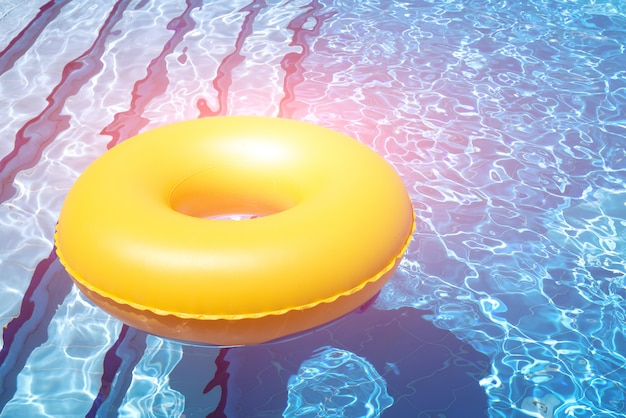 Tubo interno amarelo inflável flutuando nas águas azuis claras na piscina com luz brilhante